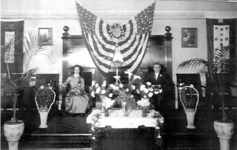 John G. and Florence Lake in 1918 at their new church in Spokane, north of the Spokane Falls and east of the courthouse. For three years prior to having their own facility, they met in the Masonic Temple just south of the River.